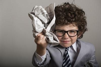 新聞紙をくしゃくしゃにする子供