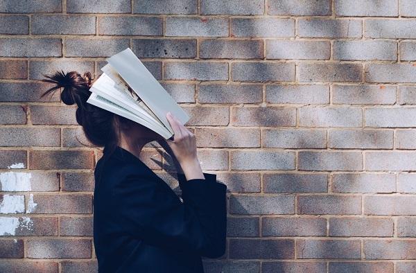 本を頭におく女性