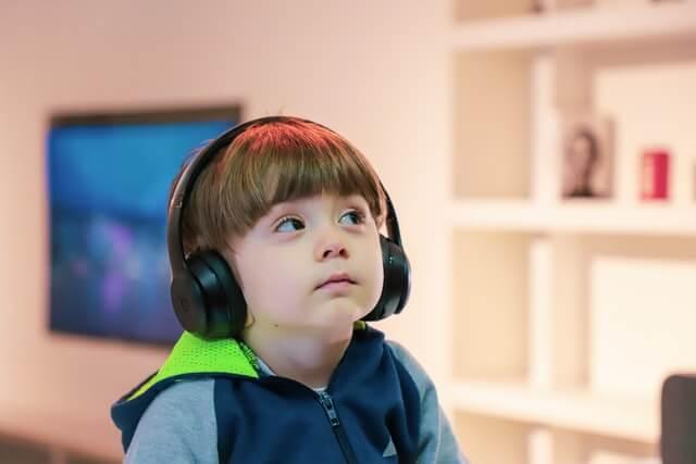 ヘッドホンで音楽を聴いている子供