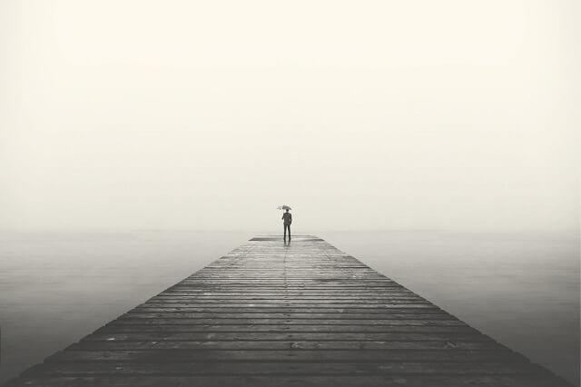 幻想的な一本橋で傘をさす男性と曇った感じ