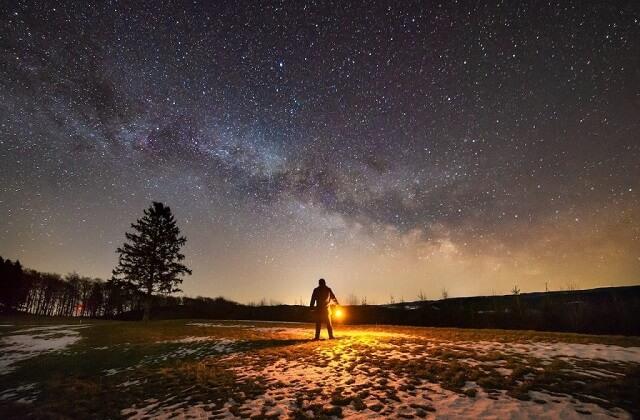 ランタンを持つ男性と星空
